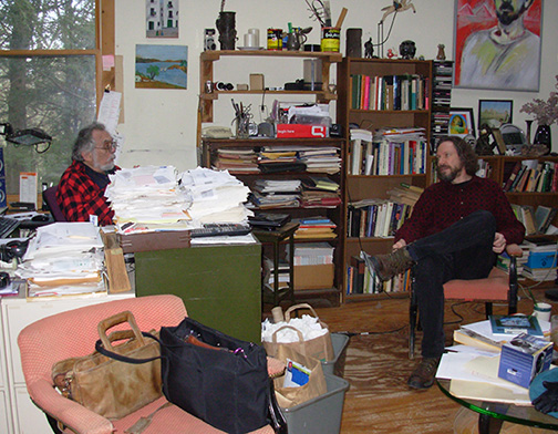 A photo of Robert Schoch and John Anthony West sitting and speaking with other  					in JAW's home in New York