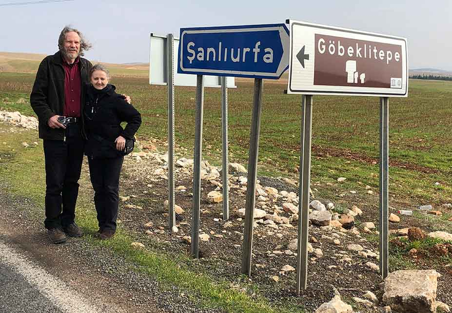 Image of Robert Schoch and Catherine Ulissey beside road signs pointing to  					Şanlıurfa and Göbekli Tepe.