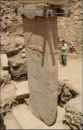 Image of central pillar of Enclosure D at Göbekli Tepe, showing anthropomorphic  				features