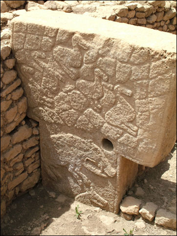 Image of Göbekli Tepe pillar showing detailed relief carvings as well as   				abutting secondary surrounding walls