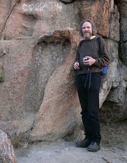 Image of Robert Schoch standing by the so-called giant's footprint in South Africa
